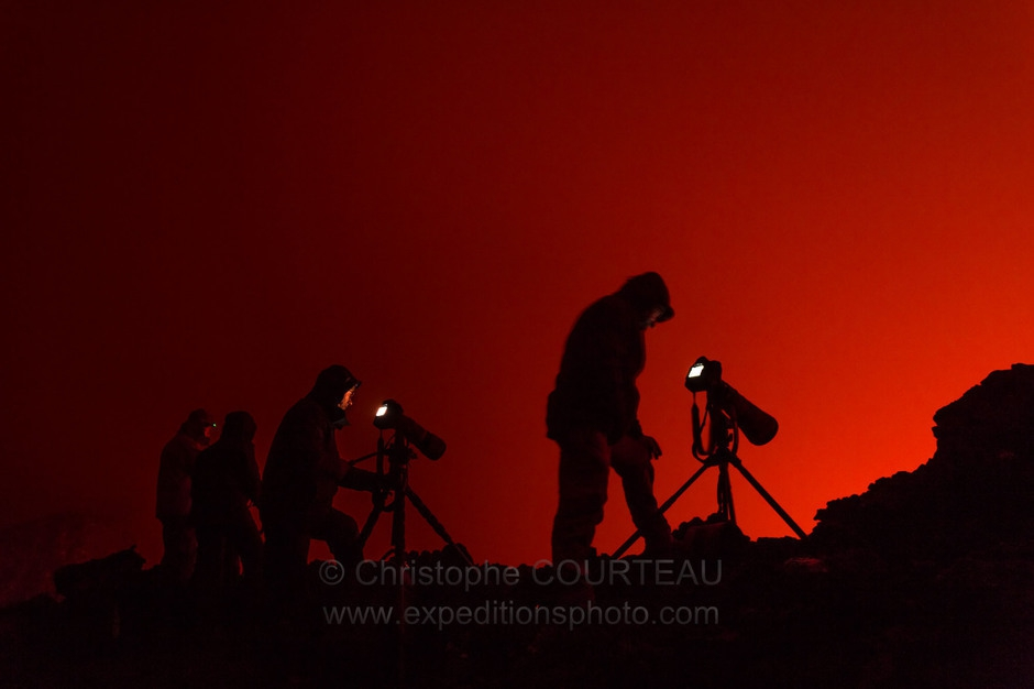 Photographers silhouettes taking photos of the Lava Lake activity of the Nyiragongo Volcano,  from the summit